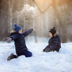 two-brothers-sits-on-the-snow-and-plays-and-laughi-S8EUGNR